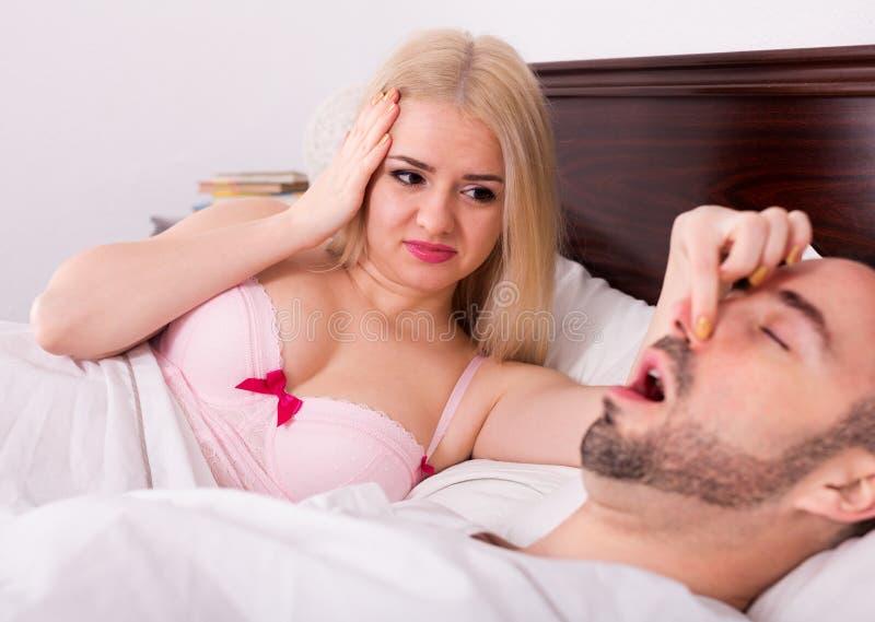 Fru med maken som snarkar i sömn royaltyfri bild