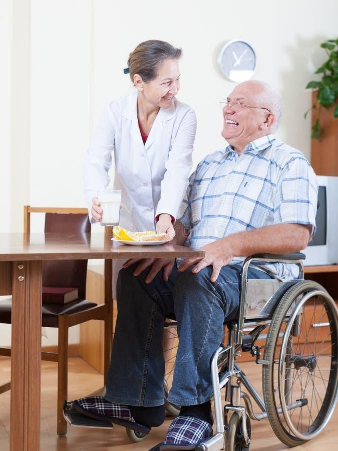 Fru som hjälper hennes make i rullstol royaltyfria foton
