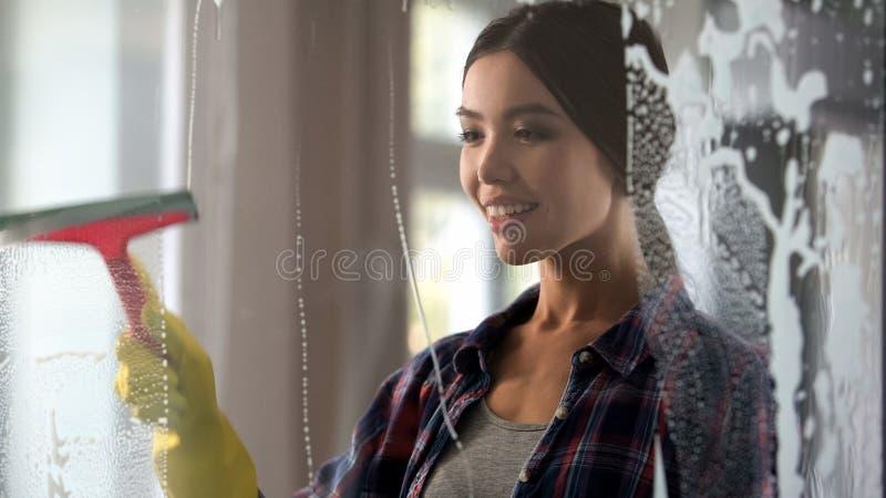 Fru som torkar den glass dörren av hennes lägenhet från damm och fläckar, hus-stolt kvinna arkivfoton