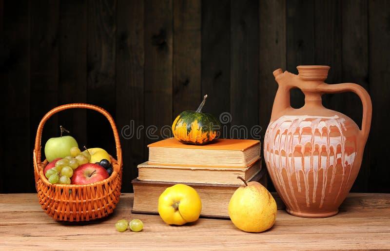 Frucht, Bücher und keramische Karaffe stockfoto