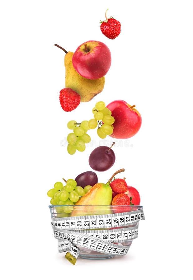 Frucht, die in eine Glasschüssel auf Weiß fällt stockbilder