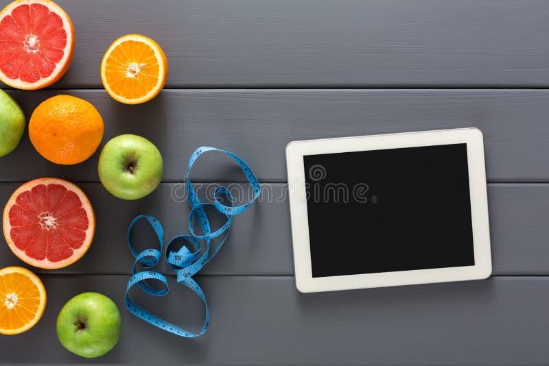 Frucht, messendes Band und leeres Tablettenmodell stockbilder
