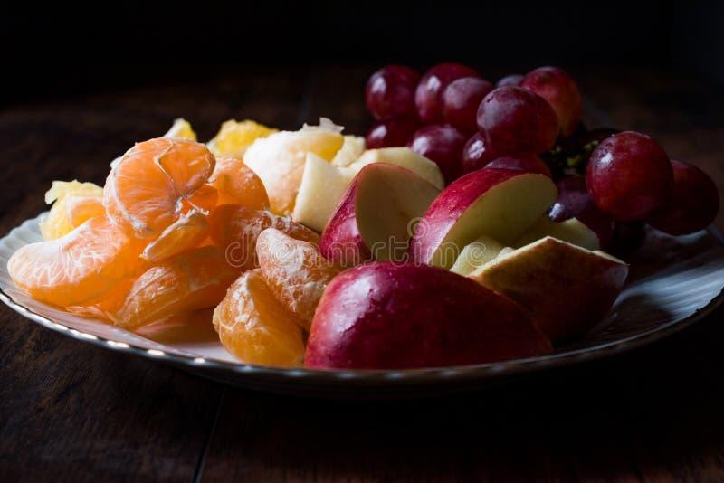 Frucht-Platte mit purpurroter Traube, Orange, Mandarine und Apple Dunkles schwermütiges stockfoto