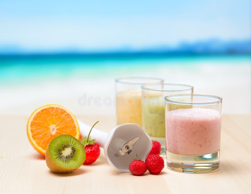 Frucht Smoothie auf Holztisch auf tropischem Strand stockbild