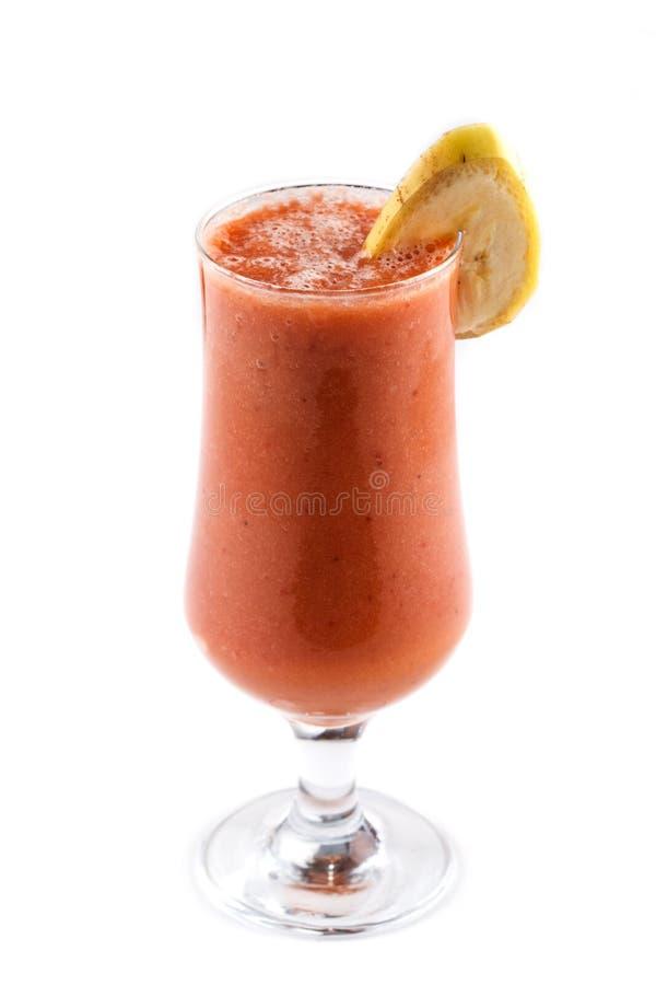 Frucht und Milch Smoothie in einem Glas auf dem Bein verziert mit Bananenscheibe auf einem lokalisierten weißen Hintergrund stockfotografie