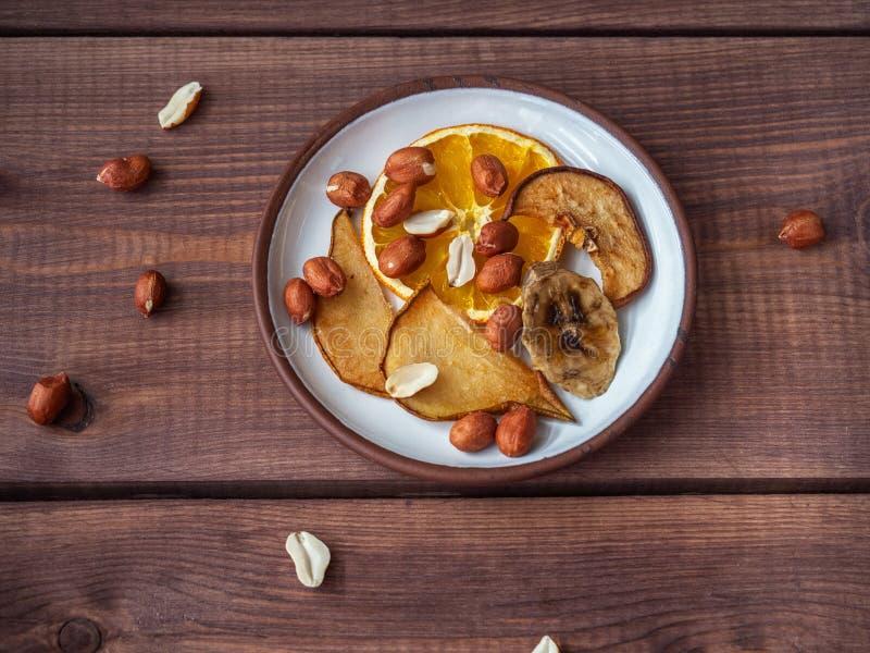 Fruchtchips ohne Zucker und Zus?tze auf einem Pl?ttchen und Erdn?ssen, zerstreut nahe bei der Platte und auf der Platte, stockbild