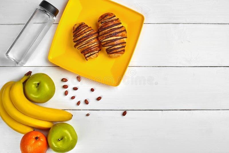 Fruchtfrühstück mit freiem Raum auf Holztisch Hörnchen, Banane, Apfel, Nüsse und eine Flasche Wasser Beschneidungspfad eingeschlo lizenzfreie stockfotos