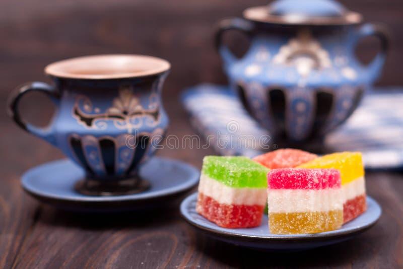 Fruchtgelee auf hölzernem Hintergrund mit Tasse Tee stockfotografie