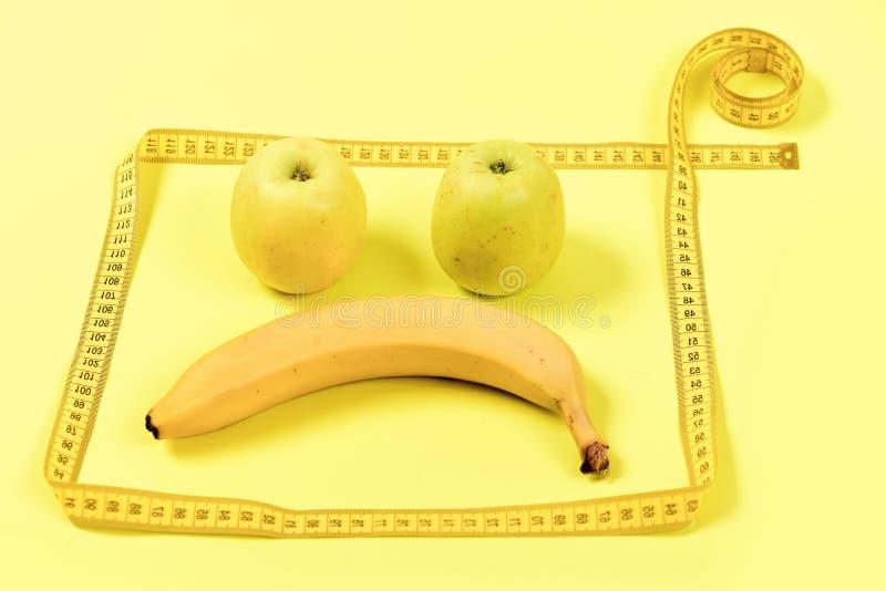 Fruchtgesicht mit traurigem Ausdruck gestaltet mit messendem Band stockbild