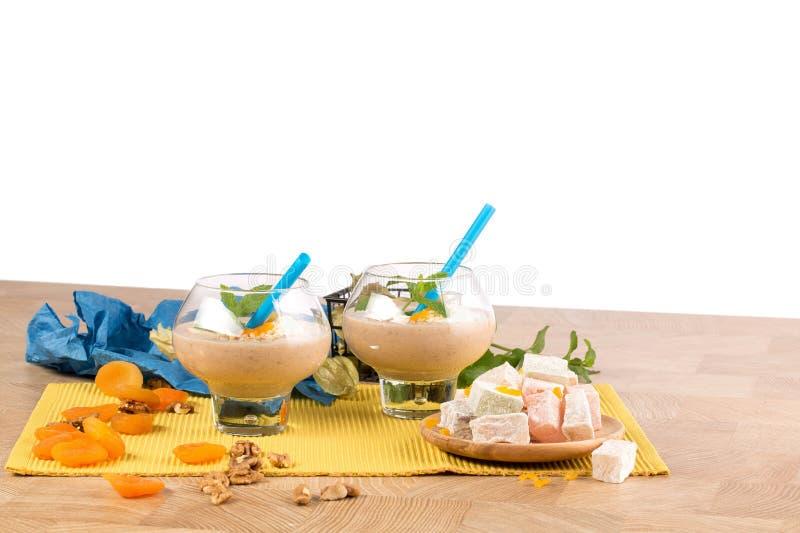 Fruchtige Smoothies in den Nachtischgläsern auf einem weißen Hintergrund Cocktails nahe bei türkischer Freude und getrockneten Ap stockfotografie