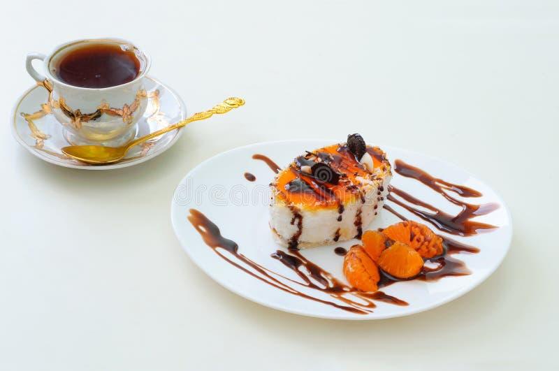 Fruchtkuchen mit Schokolade und Orange und eine Tasse Tee lizenzfreie stockfotos