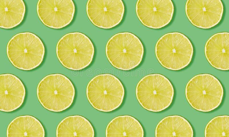 Fruchtmuster von den Scheiben des Kalkes auf grünem Hintergrund lizenzfreie stockfotos