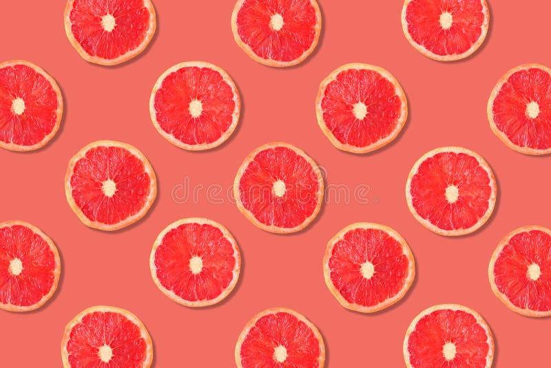 Fruchtmuster von Scheiben der rosa Pampelmuse auf einem rosafarbenen Farbhintergrund stockbild