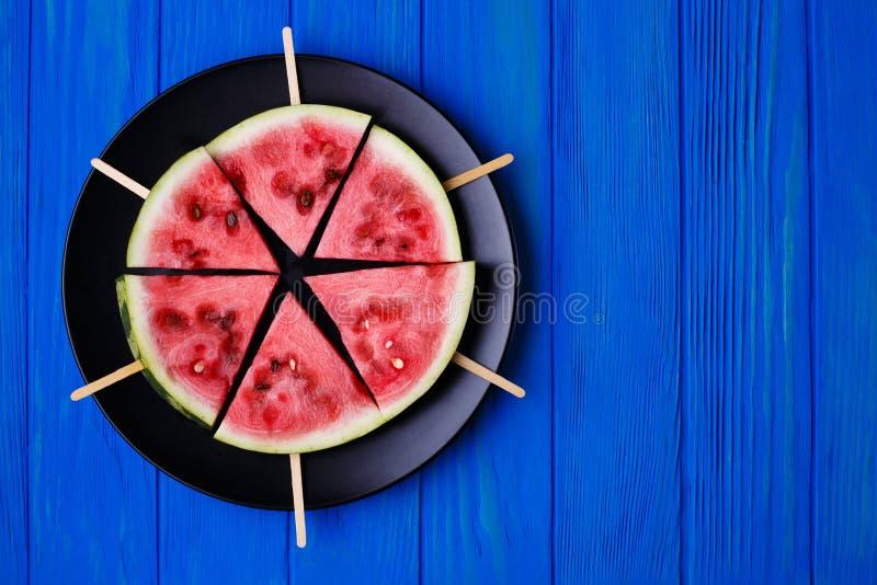 Fruchtplatte Wassermelonenscheibe popslices auf einer Platte auf blauem woode lizenzfreies stockfoto