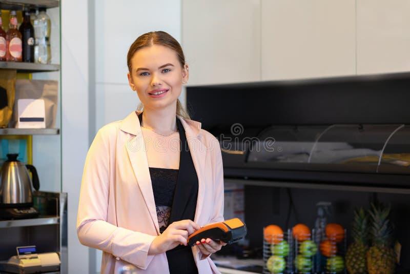 Fruchtsaft-Kneipenbesitzerstellung am Zahlschalter, der eine Zahlungsmaschine der elektronischen Karte - lächelnden Holdingradioa stockfotos