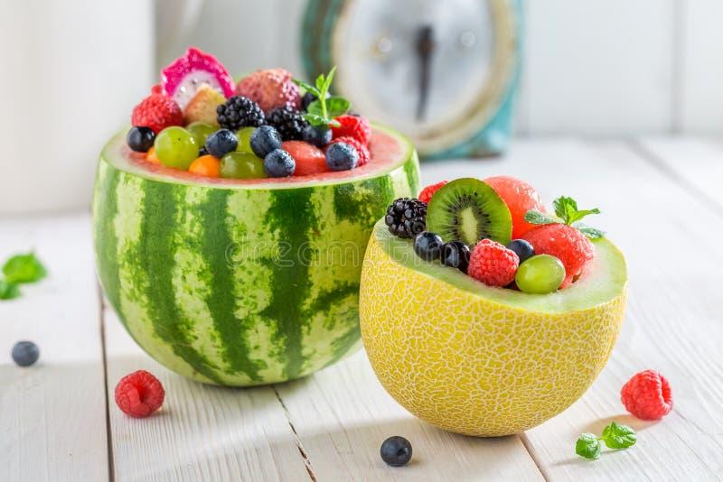 Fruchtsalat in der Wassermelone und in der Melone mit Beerenobst stockbild