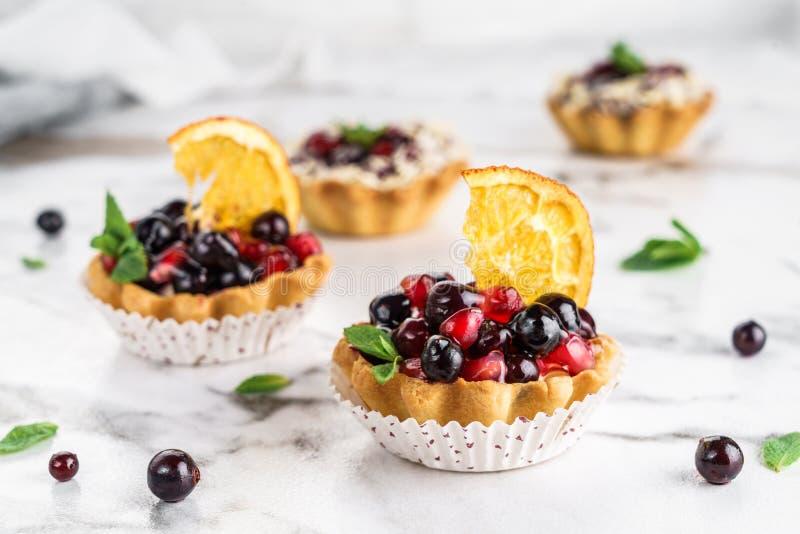 Fruchttörtchen mit Orange, Granatapfel, Korinthe und Creme, Kuchen und Süsse auf hellem Marmorhintergrund K?stlicher Nachtisch stockfotografie