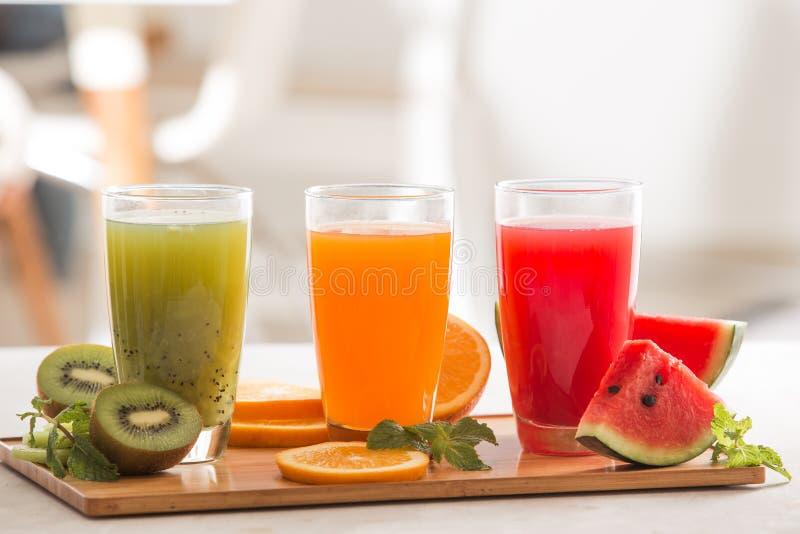 Frui tropical orange vert rouge en verre du smoothie trois frais de jus photo libre de droits