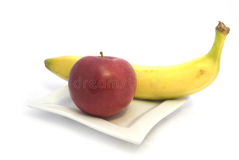 Fruit. Red apple and a yellow banana lies on a white plate royalty free stock image
