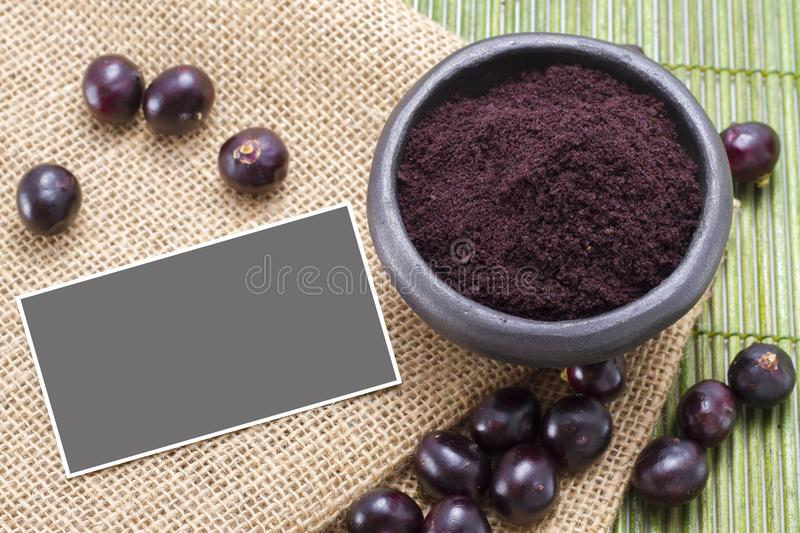 Fruit and acai powder in bowl on wooden stock photography