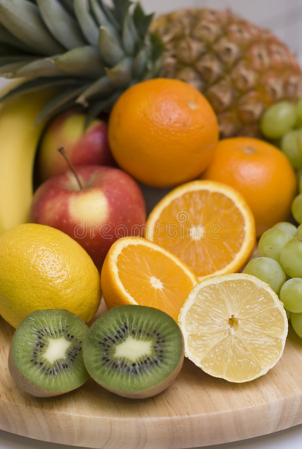 Fruit background. Colourful composition consisting of fresh fruit. The ingredients are: pineapple, bananas, kiwis, grapes, oranges royalty free stock photography