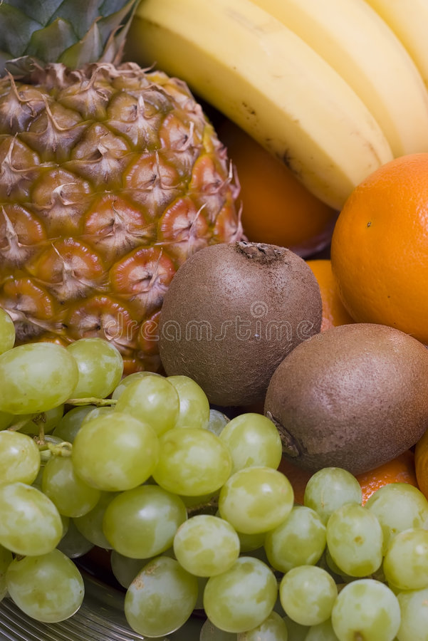 Fruit background. Colourful composition consisting of fresh fruit. The ingredients are: pineapple, bananas, kiwis, grapes, oranges stock photos