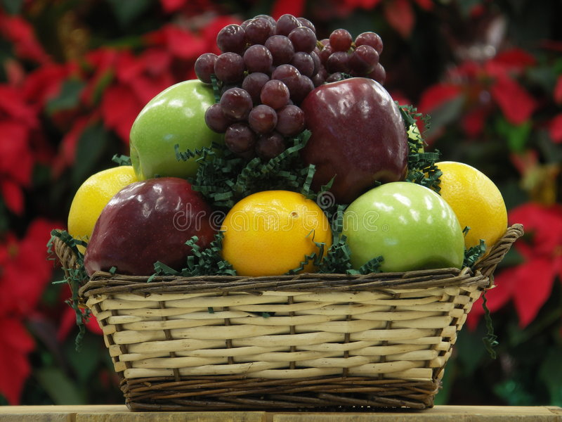 Fruit basket. With poinsettas as backdrop stock photo
