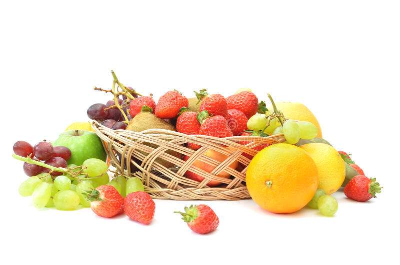 Fruit basket. Various types of fruit inside and around a basket on a white background royalty free stock photos