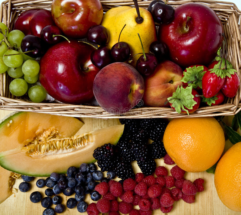 Fruit basket. A delicious selection of fruit overflowing from a basket royalty free stock images