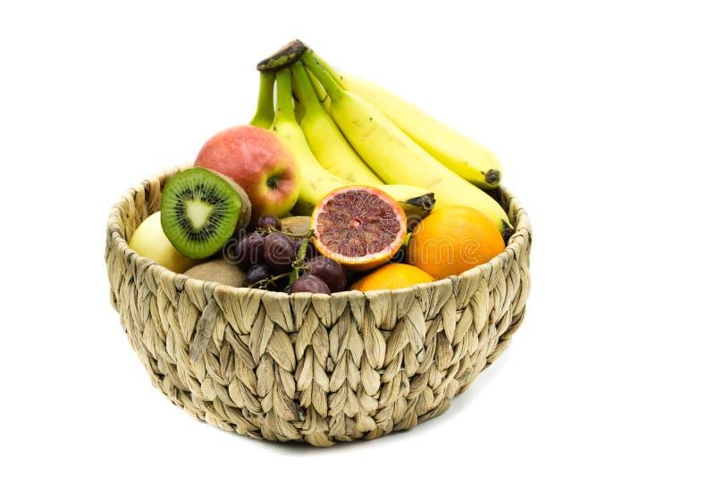 Fruit basket with bananas, apples, oranges and kiwis isolated on white background stock photography