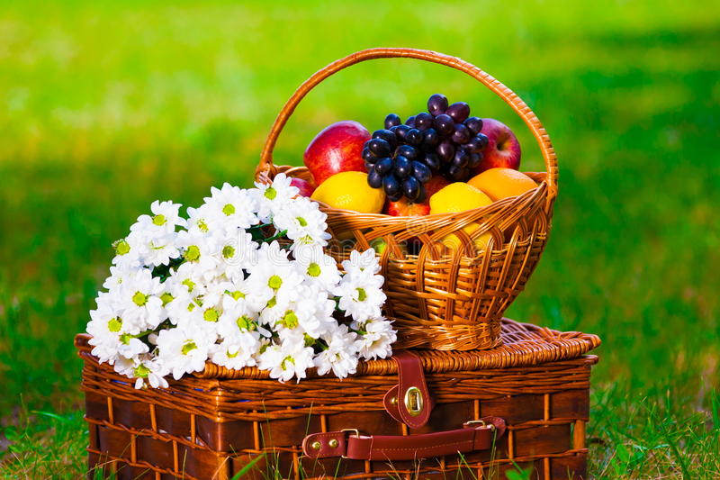 Fruit basket and flowers. Beautiful and delicious fruit basket and flowers royalty free stock photo