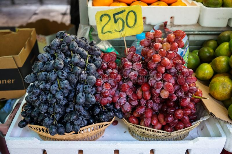 Fruit baskets of fresh sweet black and red grapes selling in local market with price tag stock photo
