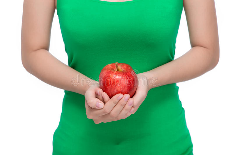 Fruit. Beautiful female hand holding and showing a red apple on stock images