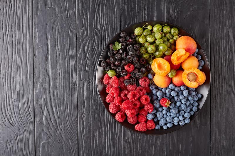 Fruit and berries platter, top view. Fruit and berries platter with fresh organic gooseberry, red and black raspberry, blueberry, apricot slices on a black royalty free stock image