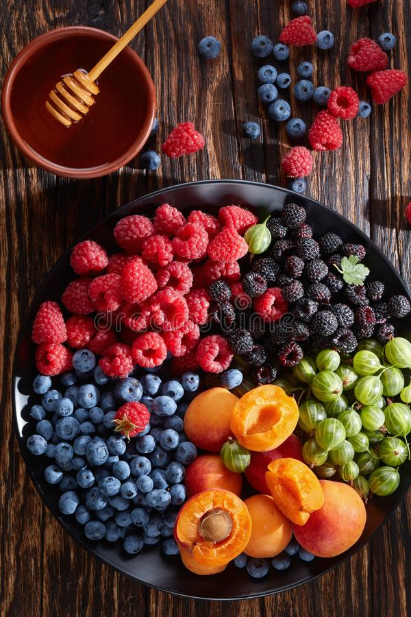 Fruit and berries platter, top view. Fruit and berries salad with fresh organic gooseberry, red and black raspberry, blueberry, apricot slices on a black plate stock photo