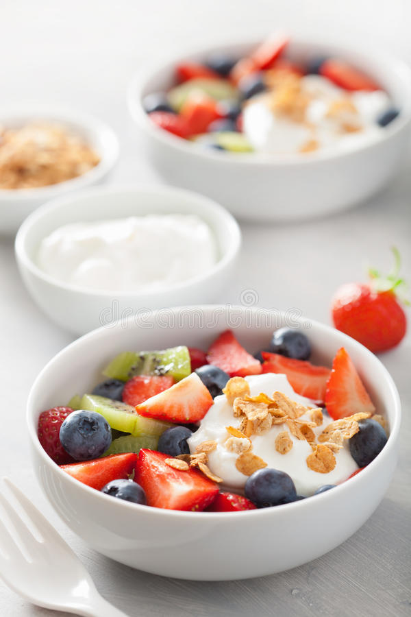 Fruit berry salad with yogurt and granola for healthy breakfast royalty free stock images