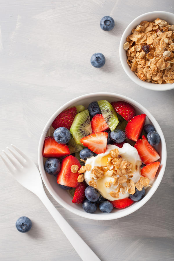 Fruit berry salad with yogurt and granola for healthy breakfast stock photos