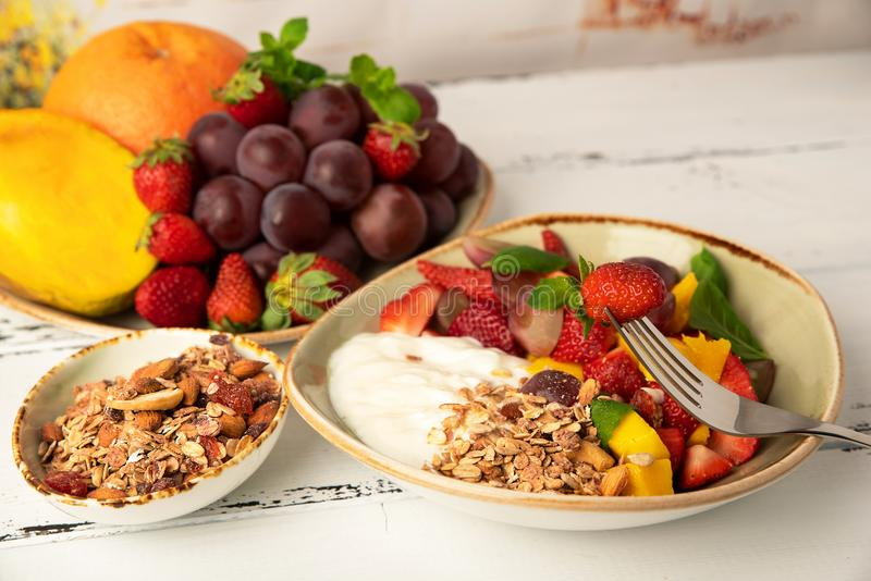 Fruit berry salad with yogurt and granola for healthy breakfast stock images