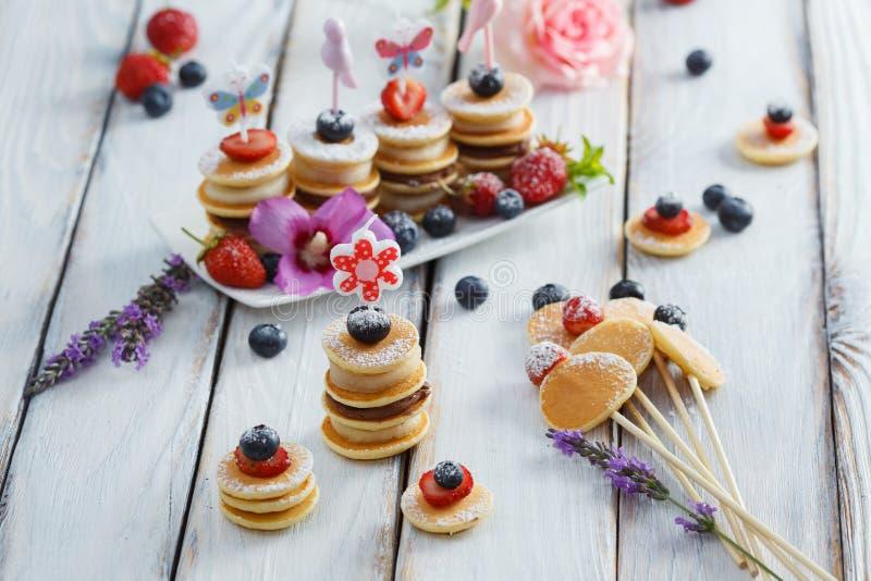 Fruit, bes en pannekoek canapes op witte houten lijst stock afbeelding