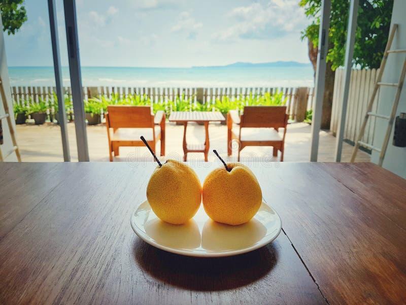 Fruit bienvenu dans la chambre à coucher d'hôtel avec la plage de terrasse et de mer à l'arrière-plan photos libres de droits