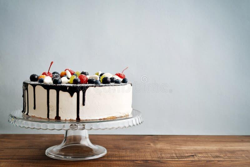 Fruit birthday cake. On cake stand over blue background royalty free stock image