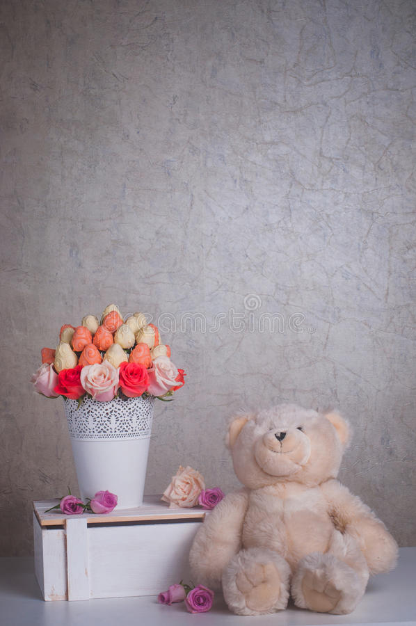 Fruit bouquet decoration with teddy bear toy on the table. Fresh strawberry covered by pink and white chocolate with rose flowers designed as a fruit bouquet in stock images