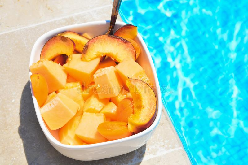 Fruit in a bowl by the pool. Fruit salad, healthy breakfast. Colorful fruit peach and melon, summer concept royalty free stock photography