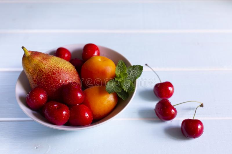 Fruit in a bowl. Red cherry, apricots, Forelle pear with fresh mint in a white bowl. Fruit in a bowl. Red cherry, apricots, Forelle pear with fresh mint in a stock photography