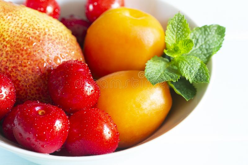 Fruit in a bowl. Red cherry, apricots, Forelle pear with fresh mint in a white bowl. Fruit in a bowl. Red cherry, apricots, Forelle pear with fresh mint in a royalty free stock photography