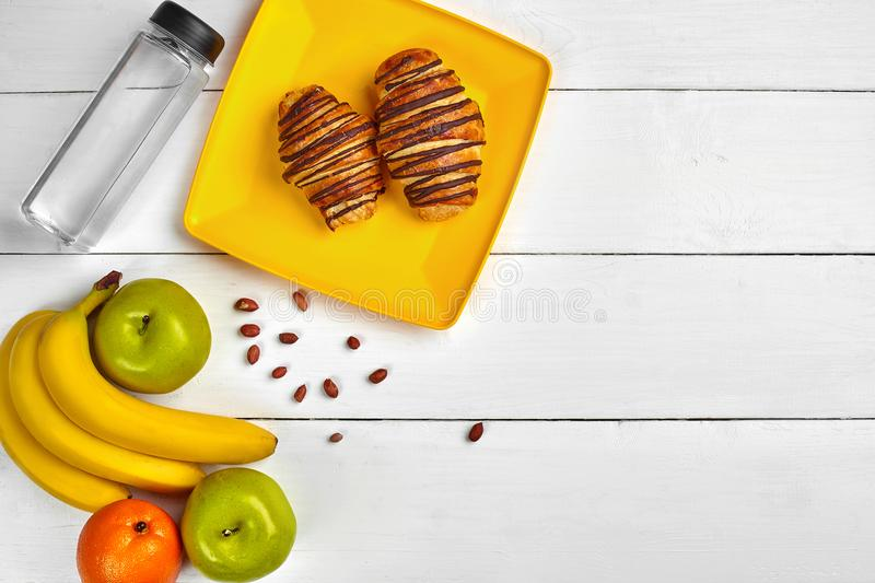 Fruit breakfast with free space on wooden table. Croissant, banana, apple, nuts and a bottle of water. Top view. royalty free stock photos
