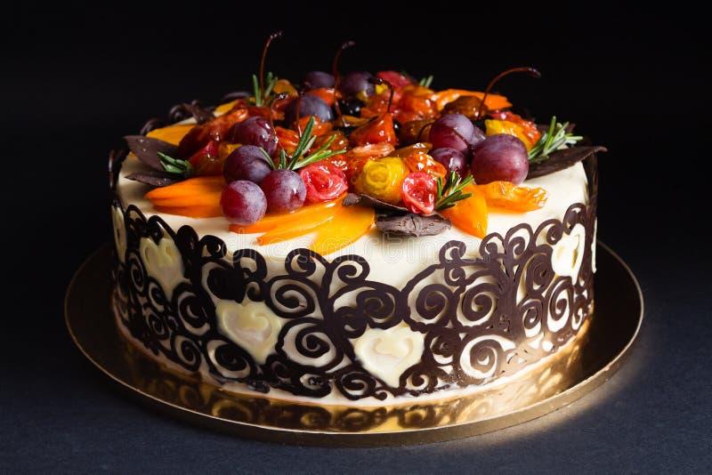 Fruit cake with chocolate border on black background royalty free stock images