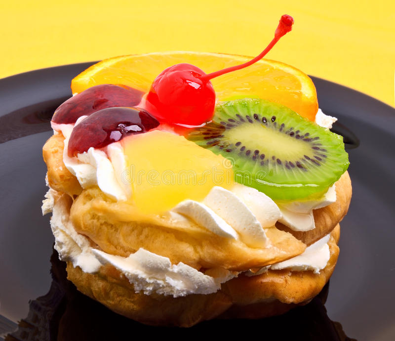 fruit cake with cream on black plate on yellow royalty free stock image