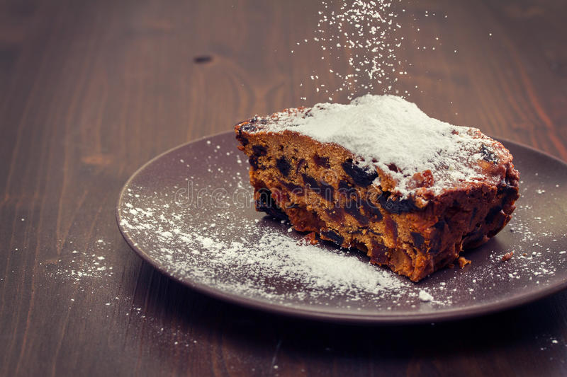 Fruit cake on dark plate. On brown wooden background stock photography