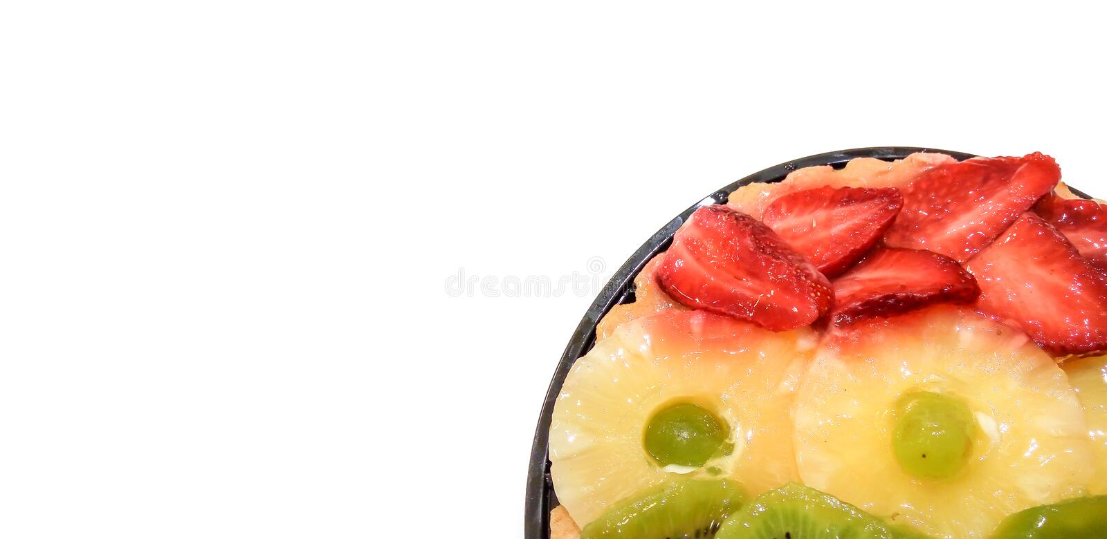 Fruit cake with oranges, kiwi, grapes, pineapple and strawberries closeup isolated on white background with place for text. stock photos
